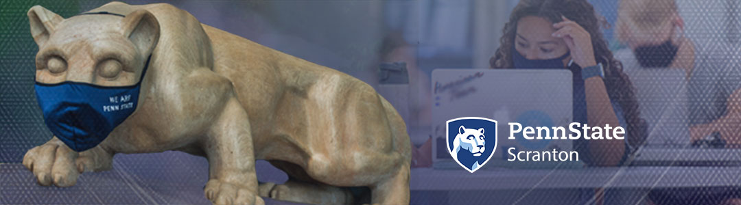 Penn State Scranton. Penn State Nittany Lion Shrine wearing protective mask. Masked Students in campus computer lab in background.